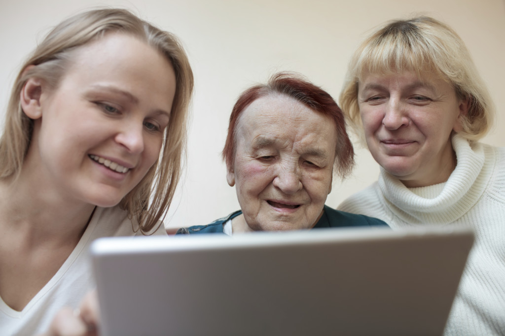 Three women of different ages smiling using a smart tablet