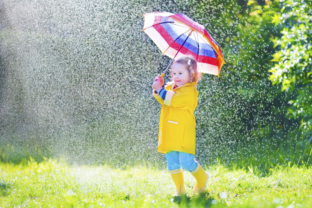 Funny toddler with umbrella playing in the rain