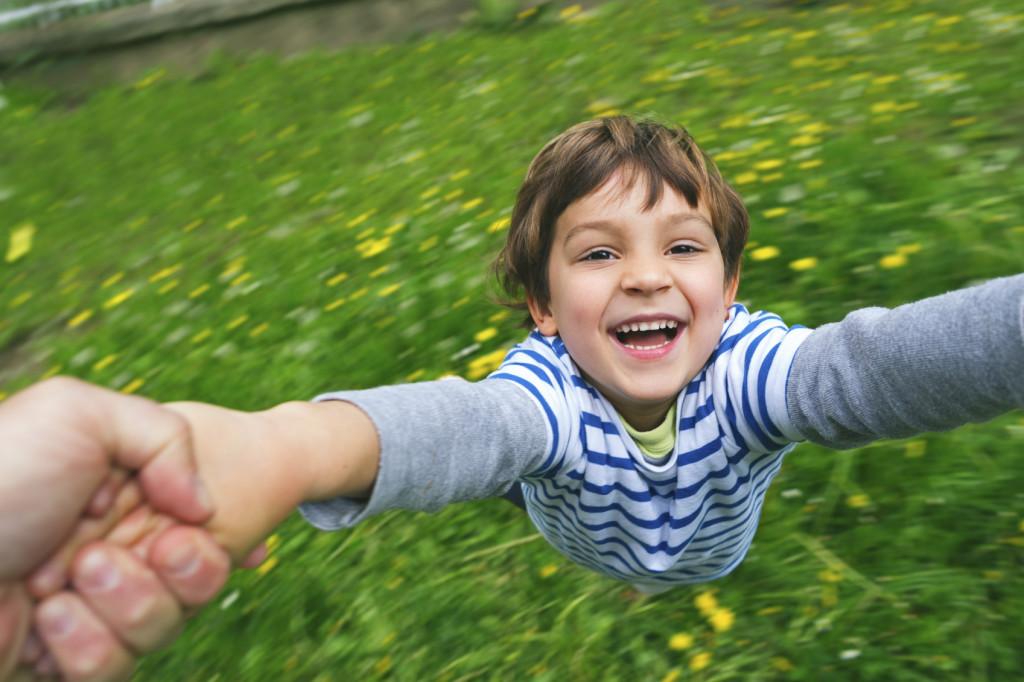 Cute boy laughing being spun around