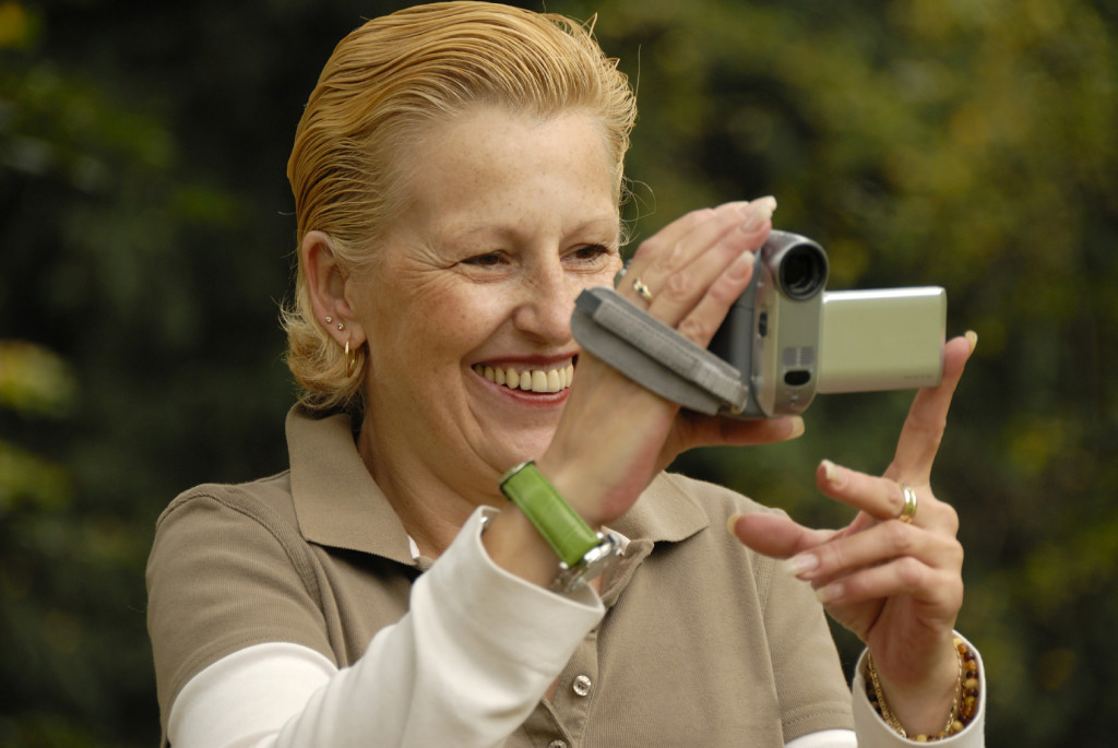 middle-aged woman filming with a handycam