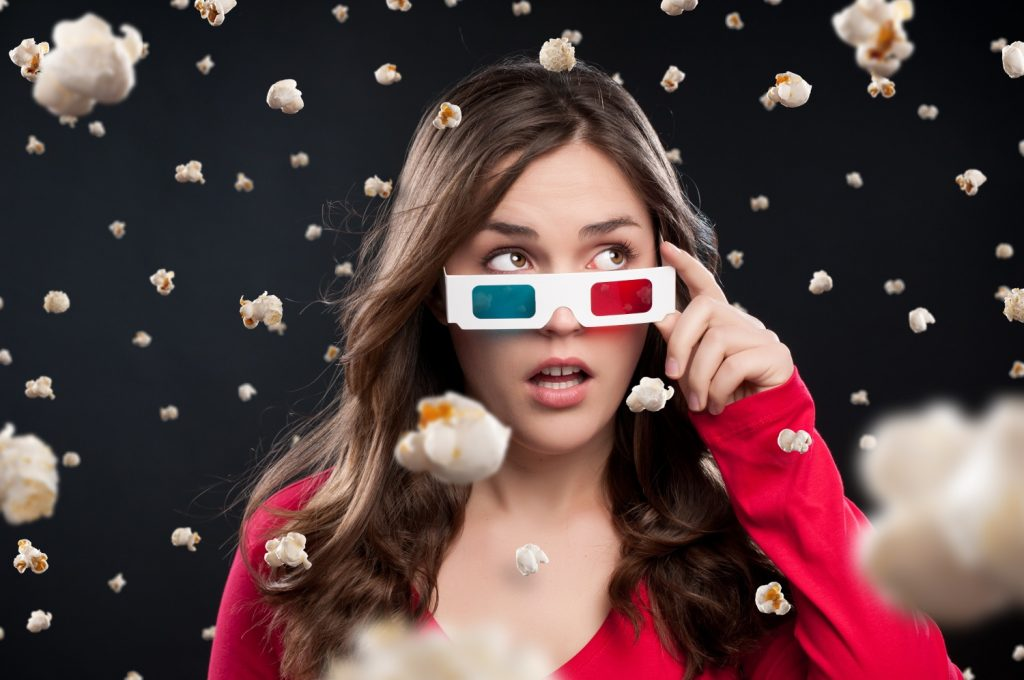 woman wearing 3D TV glasses with popcorn falling down