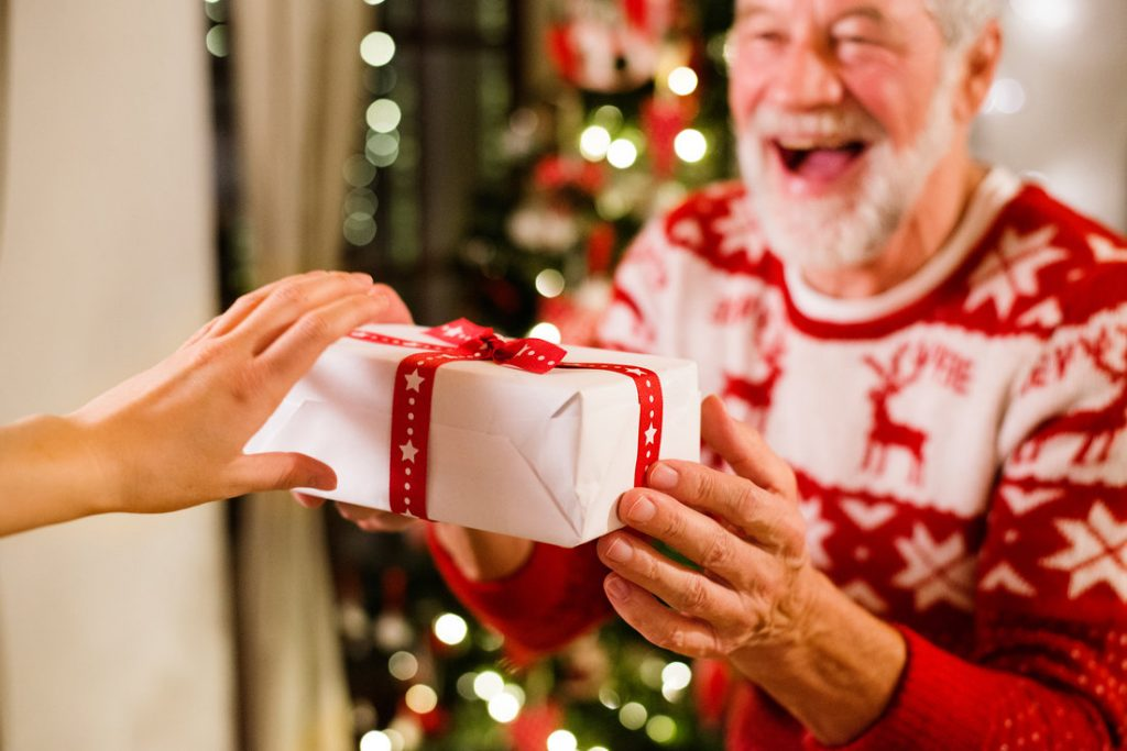 Delighted Elderly Man Receiving a Christmas Gift